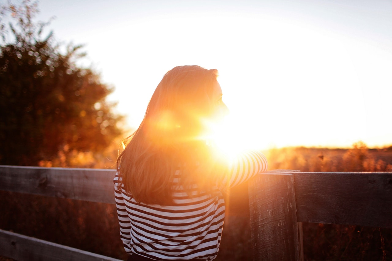 rear-view-of-woman-standing-in-balcony-during-sunset-325520